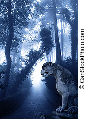 Mysterious landscape with ancient lion statue in misty forest