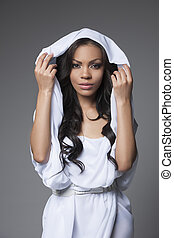 Mysterious look. Attractive African descent woman in white...