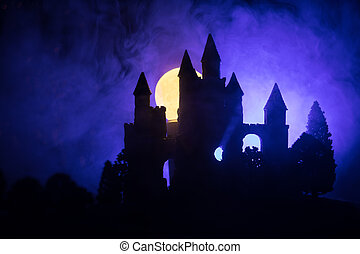 Mysterious medieval castle in a misty full moon. Abandoned gothic style old castle at night