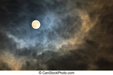 Mysterious midnight cloudy sky with full moon and moonlit clouds