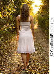 Young girl with white dress walking onto a mysterious path in the forest