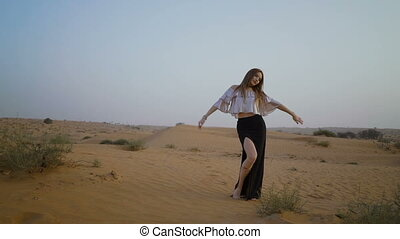 Mysterious pretty girl walks in the desert. Beautiful woman is dancing at sunset. Slow motion