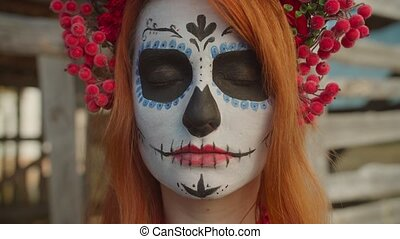 Mysterious creepy santa muerte in colorful wreath, slowly opening eyes and looking at camera with cold enigmatic stare while standing near rustic shed in countryside on halloween holiday.