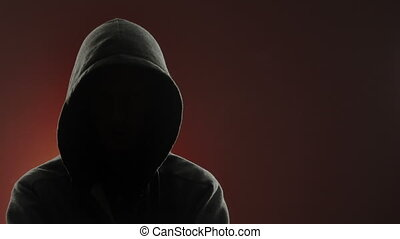 An anonymous, threatening thug wearing a hood stares at the camera in front of a red background. Centered version also available.