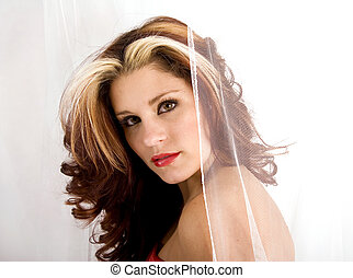 Pretty young woman posing behind white netting