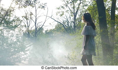 Mysterious woman wearing white dress walks in the mist fog in the woods at sunrise