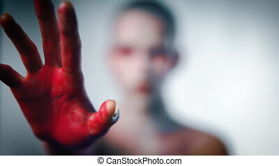 Mystery girl stretch her bloody arms forward to camera. ...