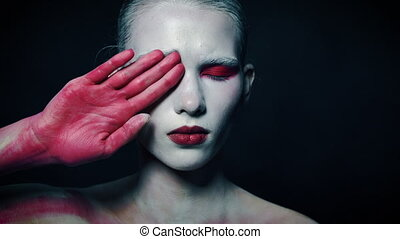 Mystery weird girl close half of her face with bloody hand. ...