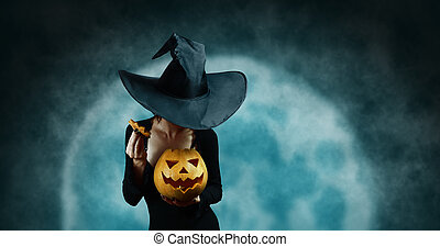 Mystery witch opening Halloween carved pumpkin on full moon...