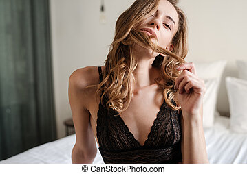 Mystery woman sitting on bed
