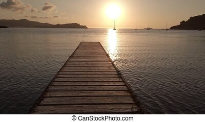 Mystic seascape at sunset with a wooden jetty of Bagnaia beach of Elba island in Italy. Concept of simplicity, purpose, direction, and infinity. copy space.