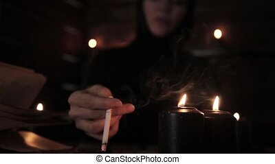 mystical beautiful female fortune teller, smoking a cigarette and laying out cards with black candlelight.