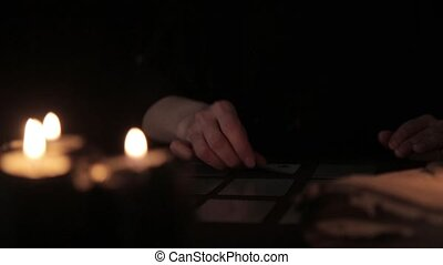 mystical beautiful woman in a black dress, divination on cards by candlelight