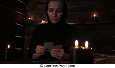 mystical beautiful woman in a black dress, divination on cards with black candlelight