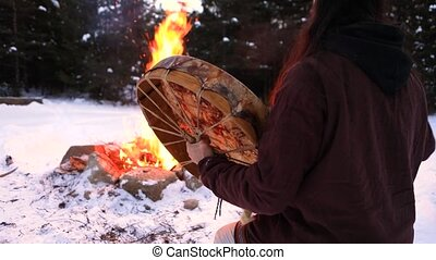Authentic raw footage by a burning fire in a forest clearing as a native man plays a sacred drum. and mystical shaman priest performs spiritual ritual