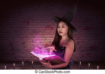 Mystical of a beautiful asian witch woman with a magic book