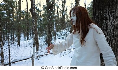 A divine shaman priest wakes from deep sleep meditation, dressed in white, guides the camera towards a peaceful snow covered forest with copy space