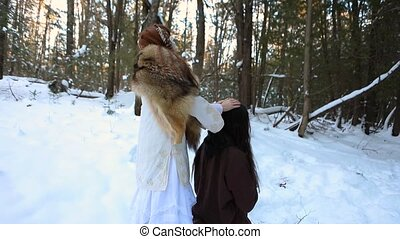 A mystical and powerful shaman oracle is seen performing a ceremonial ritual on a native tribe man. Divine soothsayer in white clothing and fur skin