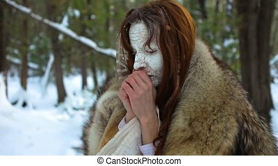 Close up footage of a native spiritual elder with traditional fur skin coat, a cracked white face and eagle feather, blowing on cold hands in winter