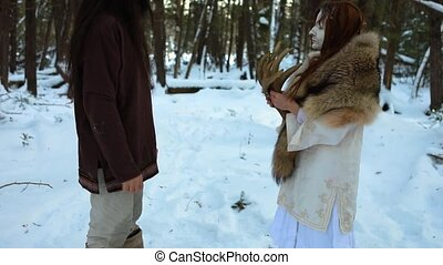 Slow motion footage as a mystical oracle hands symbolic deer antlers to a native tribesman. Spirit messenger hands totem to tribesman in woodland