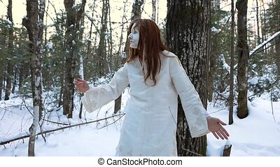 Slow motion footage as an otherworldly shaman performs spiritual movements, connection with spirit world during unusual ritual with white cracked face