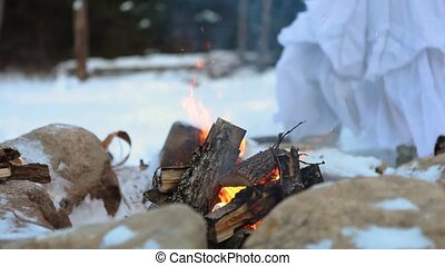 Closeup and selective focus footage of a burning camp fire as the legs of an otherworldly shaman oracle dressed in white. are seen blurry in background