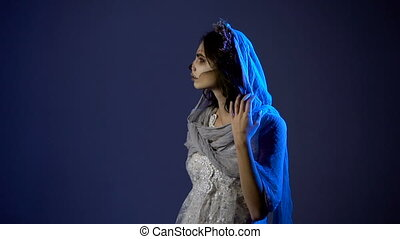 Mystical young girl is participating in Halloween party and dressed in costume of dead bride. Young woman is standing in the dark room, touching her face and staring at the camera.