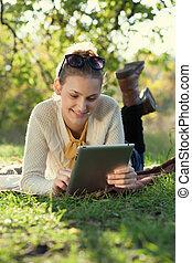 närbild, av, lycklig woman, användande, kompress, dator, utomhus