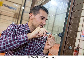 närbild, av, manlig, lockpicker, hand, fixa, dörr hantera, hemma