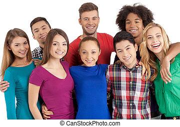 nós, é, team!, grupo, de, alegre, jovem, multi-étnico, pessoas, ficar, perto, um ao outro, e, sorrindo, câmera, enquanto, ficar, isolado, branco