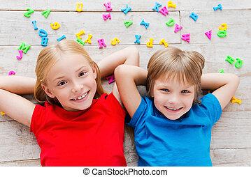 nós, amor, tendo, fun!, vista superior, de, dois, cute, pequeno, crianças prendem mãos, atrás de, cabeça, sorrindo, enquanto, encontrar-se assoalho, com, plástico, coloridos, letras, deitando, ao redor, lhes