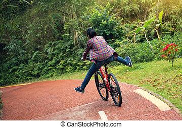 nő, biciklista, elnyomott bicikli, képben látható, erdő, nyom