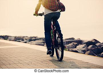nő, biciklista, elnyomott bicikli, képben látható, tengerpart