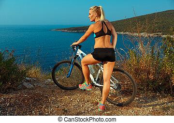 nő, biciklista, képben látható, egy, hegy bicikli, külső at, a, táj, közül, hegyek, és, tenger