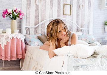 nő, fekvő, az ágyon