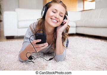 nő, fiatal, zene hallgat, fekvő, szőnyeg