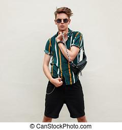 na moda, bonito, homem jovem, com, óculos de sol, em, praia, camisa, com, saco, posar, perto, parede