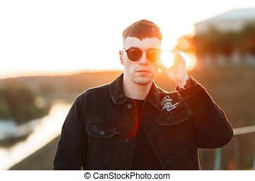 na moda, bonito, homem jovem, com, um, corte cabelo, em, elegante, pretas, denim, vestidos, corrects, óculos de sol, em, pôr do sol