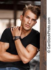 na moda, bonito, homem jovem, com, um, penteado, em, um, t-shirt preto, rua