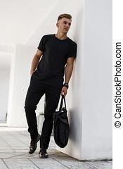 na moda, bonito, homem jovem, em, pretas, elegante, roupas, com, um, pretas, saco, posar, perto, a, parede branca