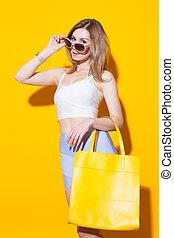 na moda, modernos, menina, posar, em, topo colorido, e, saia, com, grande, amarela, saco, ligado, dela, passe, fundo amarelo, em, a, studio., moda, beleza, girl., excitado, menina glamour, ligado, amarela, experiência., conceito