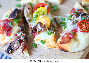 Naan bread pizza with mushrooms and bacon