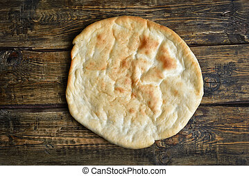 Naan bread, top view - Naan bread on wooden background, top...