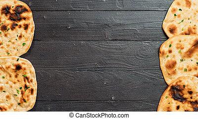 naan flatbread on dark wood, copy space, top view