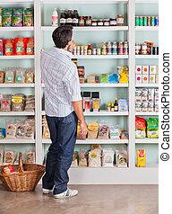 nachdenklich, mann, wählen, produkte, in, supermarkt