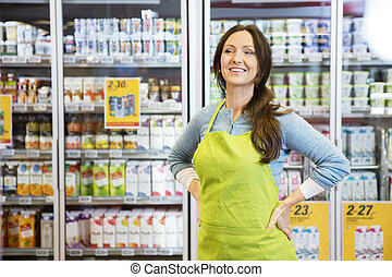 nachdenklich, verkäuferin, mit, hände, hüfte, gegen, kühlschrank