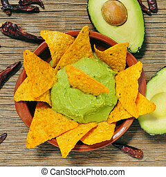 nachos and guacamole - closeup of a bowl with guacamole and...