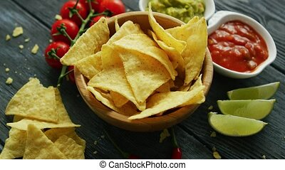Nachos and sauces on table - From above bowl of nachos with...