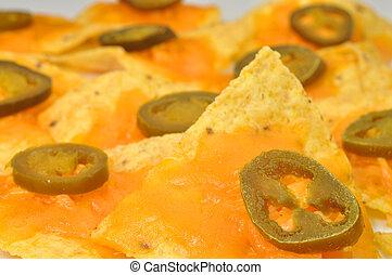 Nachos - Focus on one nacho on plate of nachos.
