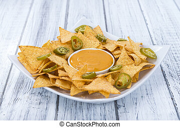 Nachos with Cheese Dip (close-up shot) on an wooden table